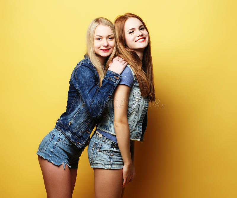 Lifestyle and people concept: Two girl friends standing together royalty free stock images