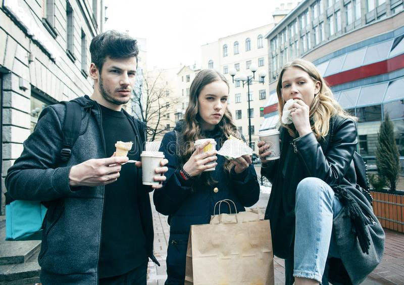Lifestyle and people concept: two girls and guy eating fast food on city street together having fun, drinking coffee royalty free stock photography