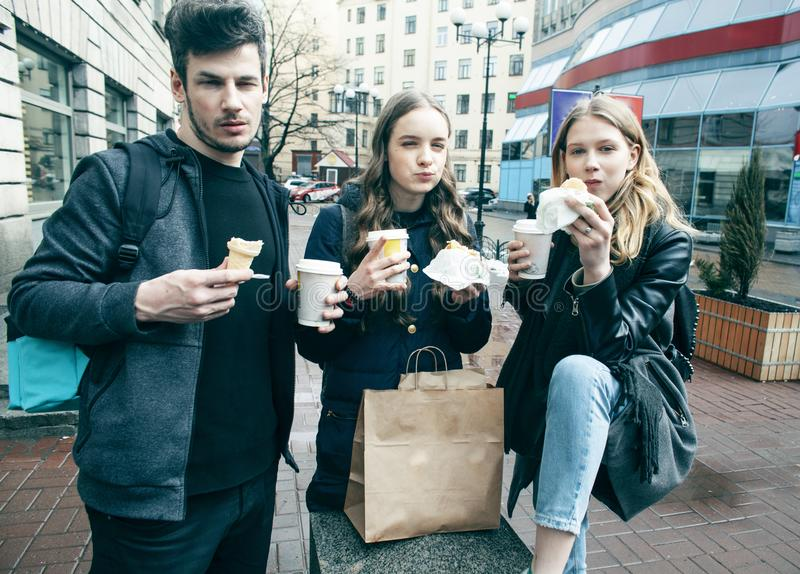 Lifestyle and people concept: two girls and guy eating fast food on city street together having fun, drinking coffee royalty free stock photos