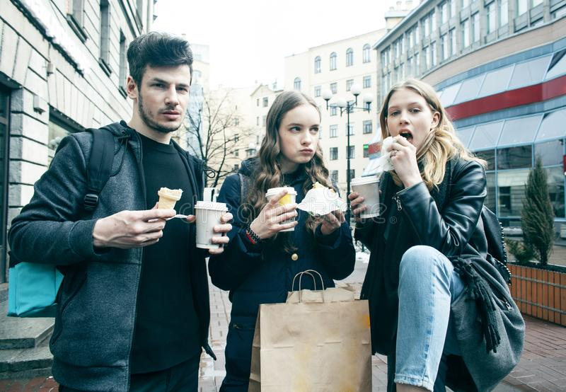 Lifestyle and people concept: two girls and guy eating fast food on city street together having fun, drinking coffee stock photography