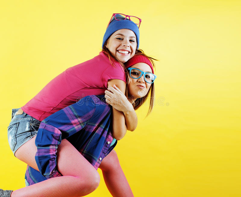 Lifestyle people concept: two pretty young school teenage girls having fun happy smiling on yellow background stock image