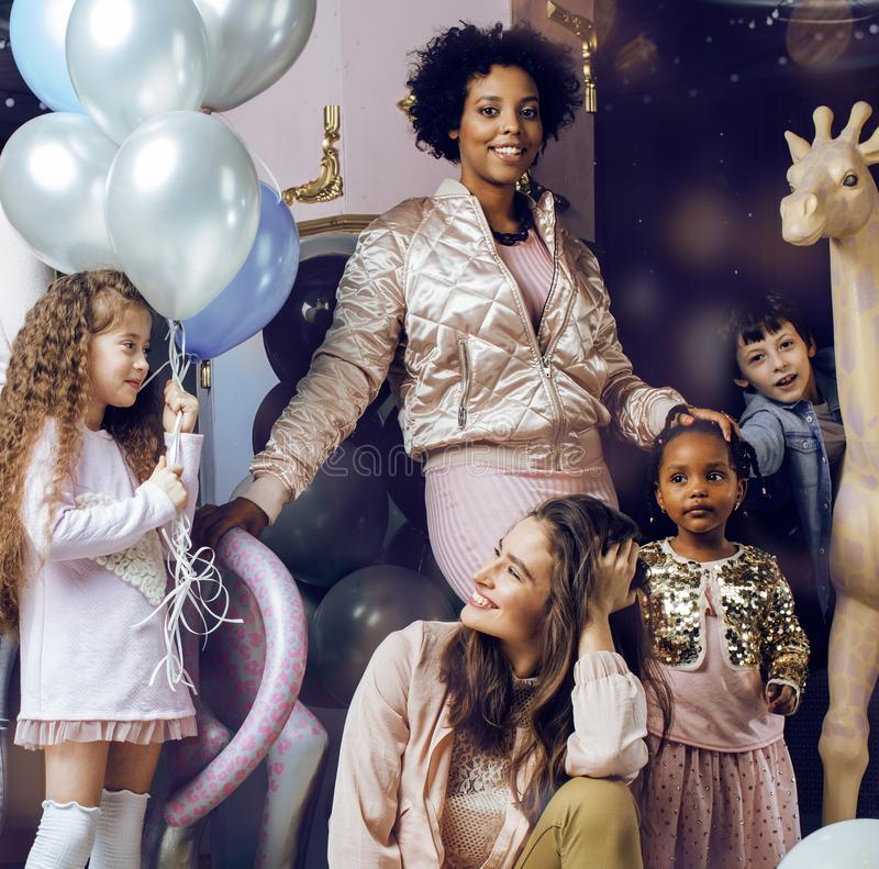 Lifestyle and people concept: young pretty diversity nations woman with different age children celebrating on birth day stock images