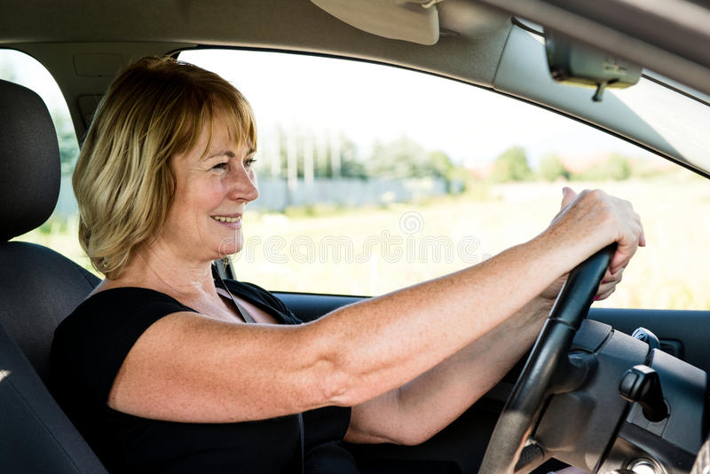 Senior woman driving car stock photography