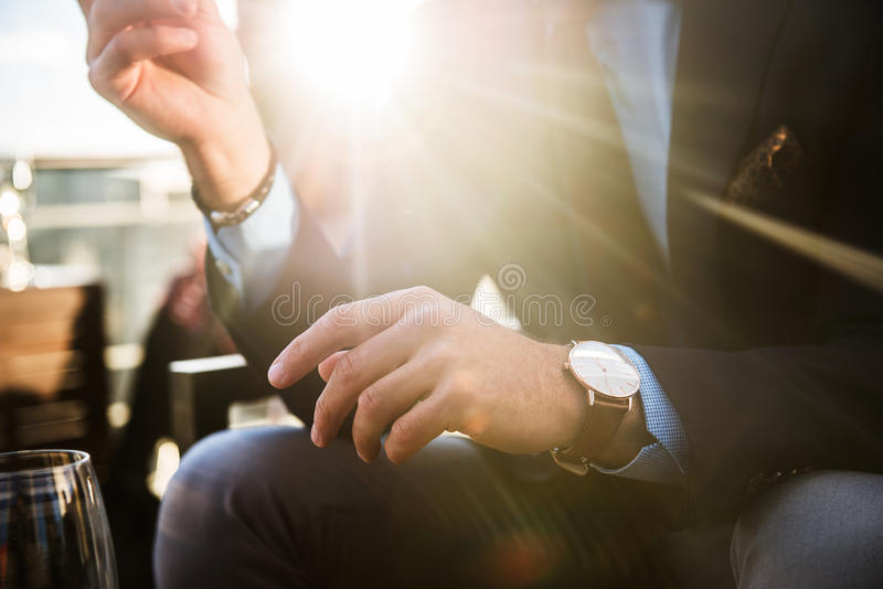 Lifestyle photo of elegant businessmen wearing luxury watch and having dinner in restaurant after successful working day stock photos