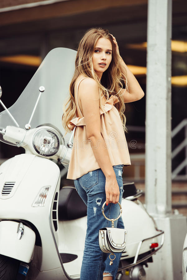 Free Lifestyle Photo Of Stylish Beautiful Woman Walking On City Street And Turning Back In Front Of Moped. Stock Photography - 97727052
