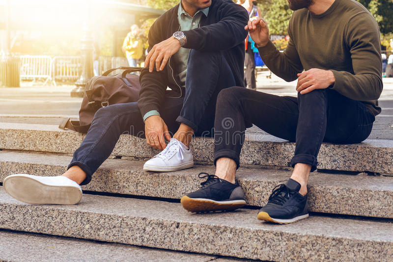 Lifestyle photo of two male friends sitting on the steps in city street and talking wearing casual street style clothes and royalty free stock photography