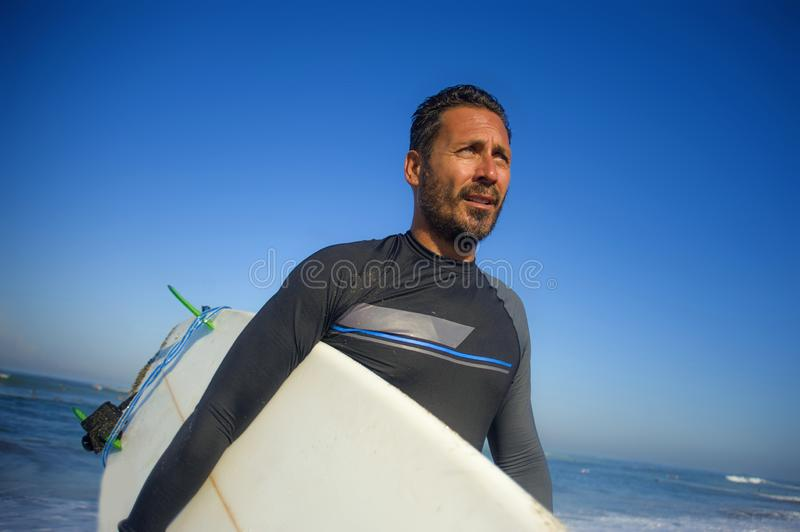 Lifestyle portrait of attractive and cool surfer man 3os to 40s in neoprene surfing swimsuit posing with surf board on the beach. Enjoying water sport and stock photos