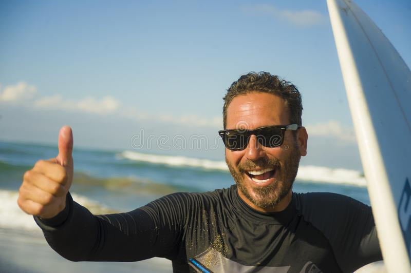 Lifestyle portrait of attractive and happy surfer man 3os to 40s in neoprene surfing swimsuit posing with surf board on the beach. Enjoying water sport and stock photos