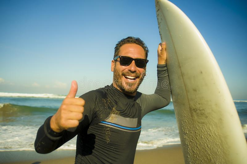Lifestyle portrait of attractive and happy surfer man 3os to 40s in neoprene surfing swimsuit posing with surf board on the beach. Enjoying water sport and stock photo