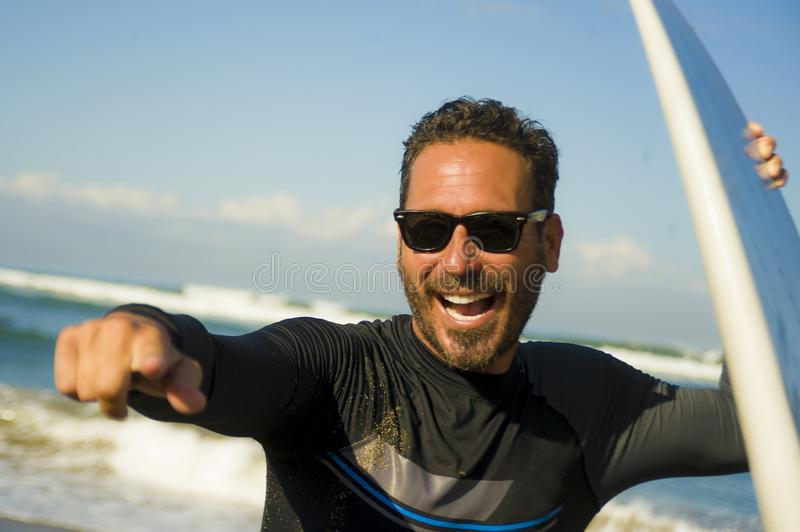 Lifestyle portrait of attractive and happy surfer man 3os to 40s in neoprene surfing swimsuit posing with surf board on the beach. Enjoying water sport and royalty free stock photo