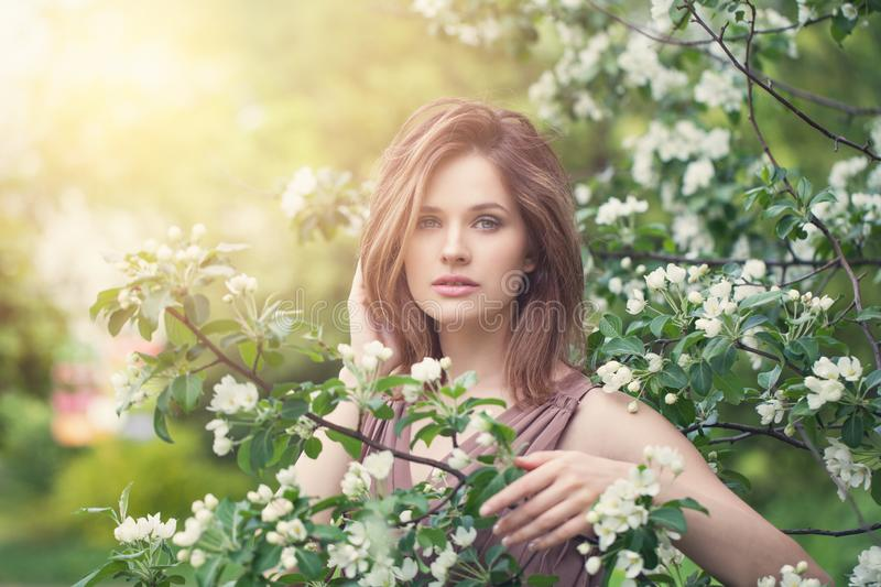 Lifestyle portrait of beautiful girl in spring blossom garden. Beauty woman on apple flowers and green leaves background stock image
