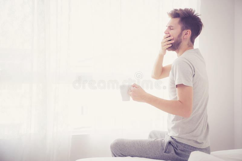Lifestyle portrait of bedroom concept: Man holding a cup of coffee and yawn with on bedroom good morning,. The lifestyle portrait of bedroom concept: Man holding stock images