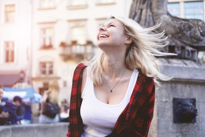 Lifestyle portrait of blonde girl wearing a rock red shirt, white t-shirt. Lifestyle portrait of fashionable happy blonde girl wearing a rock red shirt, white t stock image