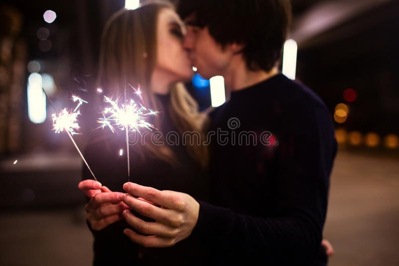 Lifestyle portrait of couple in love holding sparkling New Year fireworks on the city streets with lot of lights on background. stock photography
