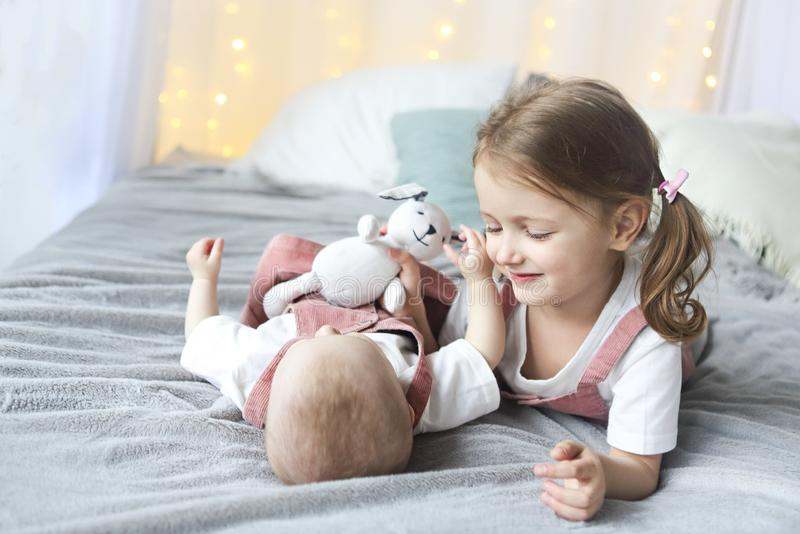 Lifestyle portrait of cute Caucasian girls sisters holding little baby on bed stock image