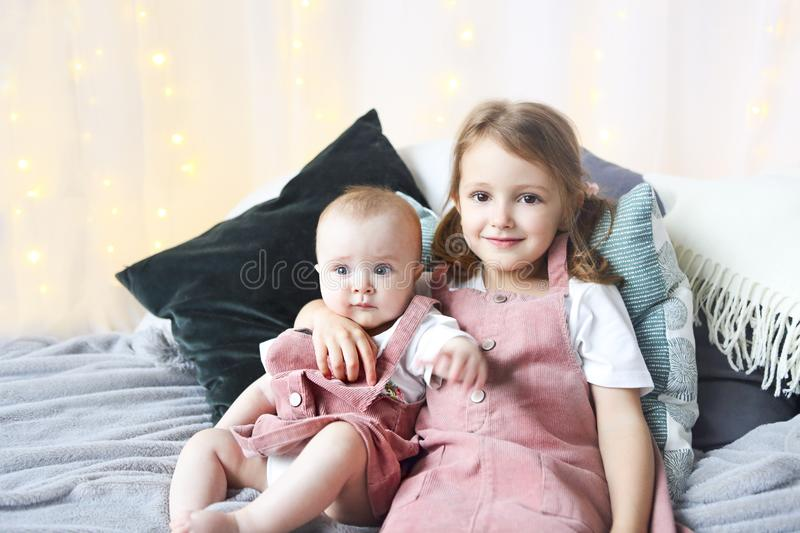 Lifestyle portrait of cute Caucasian girls sisters holding little baby on bed stock photography
