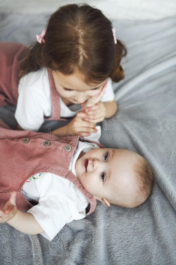 Lifestyle portrait of cute Caucasian girls sisters holding little baby on bed stock photos