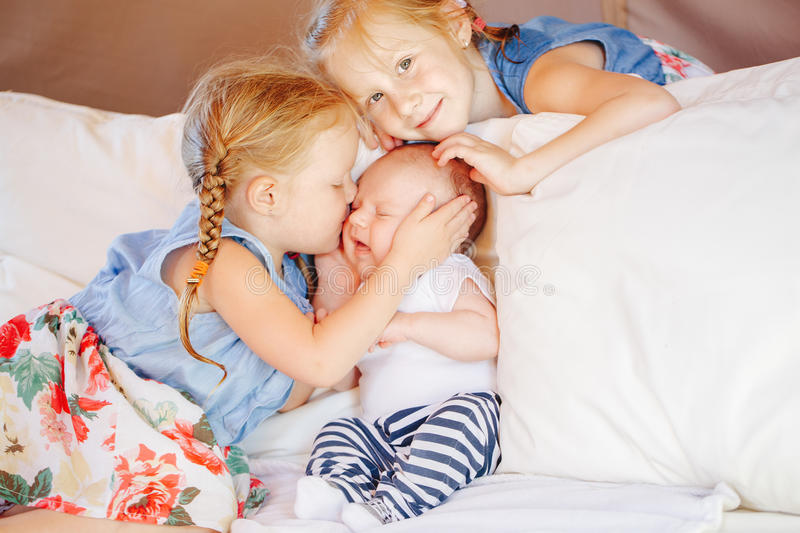 Caucasian girls sisters holding kissing little baby, sitting on bed. Lifestyle portrait of cute white Caucasian girls sisters holding kissing little baby stock images