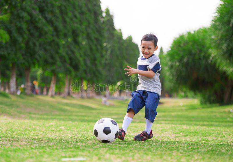 Lifestyle portrait at grass city park of 5 years old Asian Indonesian kid playing football happy and excited kicking the ball. Smiling cheerful in child sport stock photography