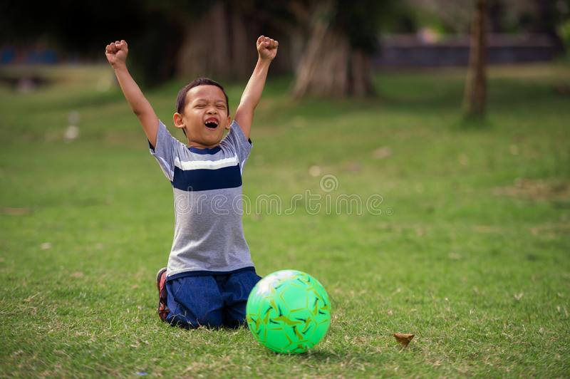 Lifestyle portrait at grass city park of 5 years old Asian kid playing football happy and excited raising arms celebrating scoring. Goal in child sport practice royalty free stock photography