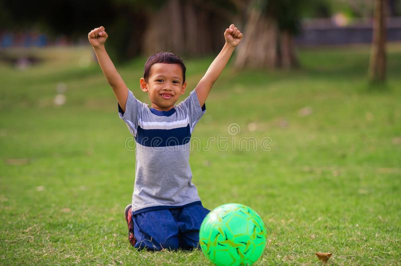 Lifestyle portrait at grass city park of 5 years old Asian kid playing football happy and excited raising arms celebrating scoring. Goal in child sport practice royalty free stock image