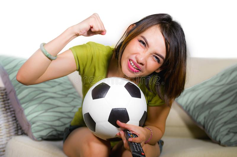 Young happy and beautiful football fan woman watching television game sitting on sofa couch holding soccer ball excited celebratin. Lifestyle portrait at home of stock photos