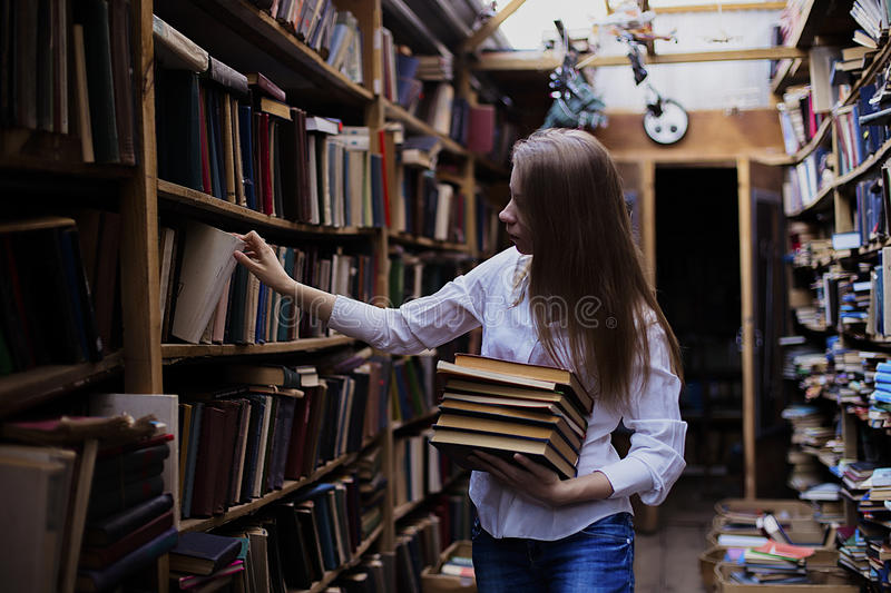 Lifestyle portrait of a lovely student girl in vintage library or bookstore. Lifestyle portrait of a lovely student girl wearing blue jeans and white shirt in royalty free stock photography