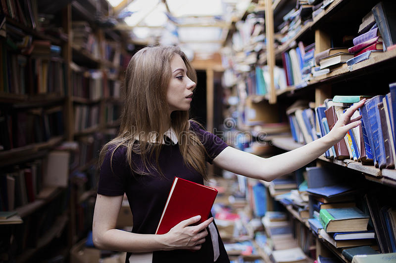 Lifestyle portrait of a lovely student girl in vintage library or bookstore. Lifestyle portrait of a lovely student girl wearing little brown dress in vintage royalty free stock photography