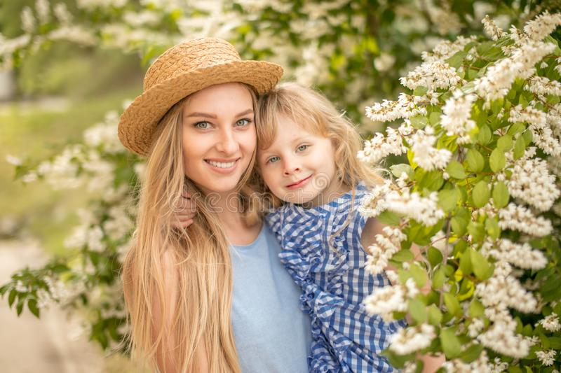 Lifestyle portrait mom and daughter in happines at outside looking at camera. Lifestyle summer portrait mom and daughter in happines at outside looking at camera royalty free stock photography