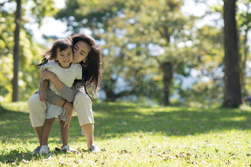 Mom and daughter in the park enjoy. Lifestyle portrait mom and daughter in happines at the outside in the meadow royalty free stock images