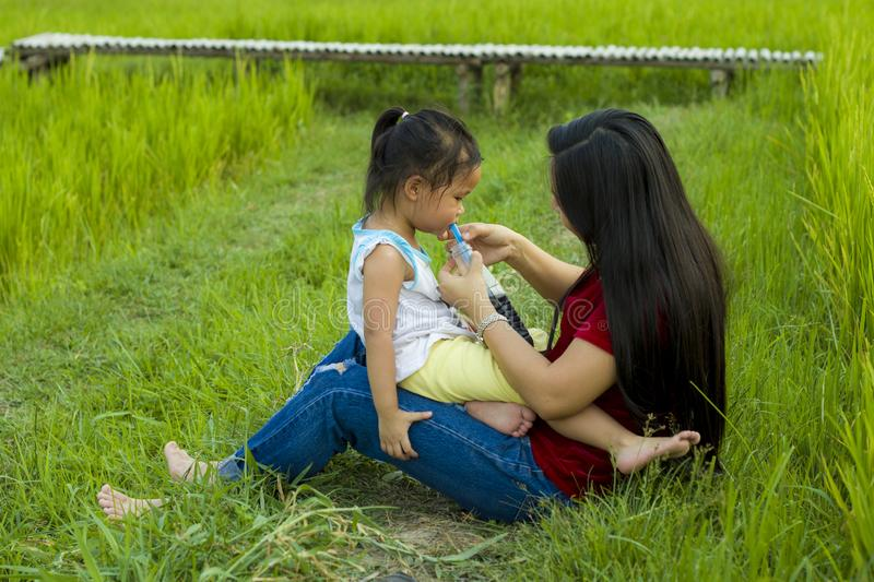 Lifestyle portrait mom and daughter in happiness at the outside in the meadow, Funny Asian family in a rice field stock photography