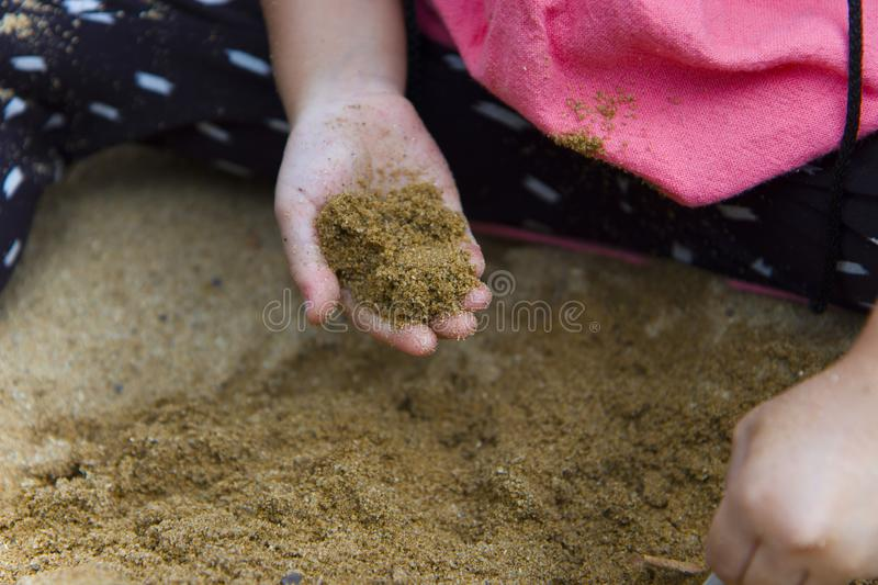 Lifestyle portrait mom son and daughter  playing with sand, Funny Asian family in a public  playground royalty free stock photo