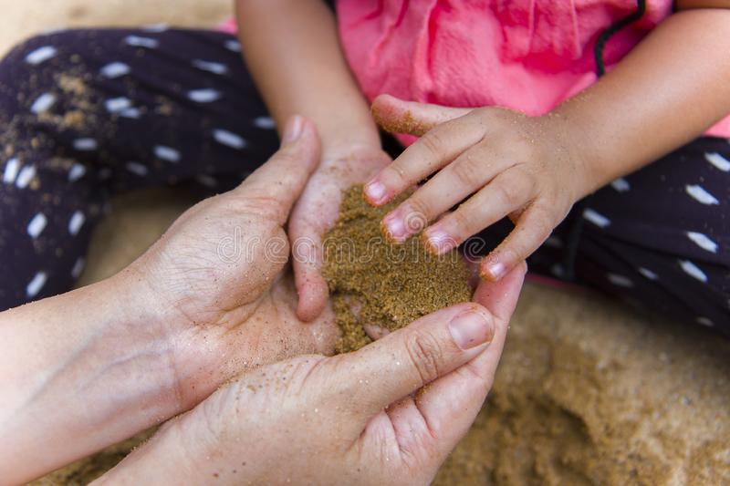 Lifestyle portrait mom son and daughter  playing with sand, Funny Asian family in a public  playground. High resolution image gallery stock photos