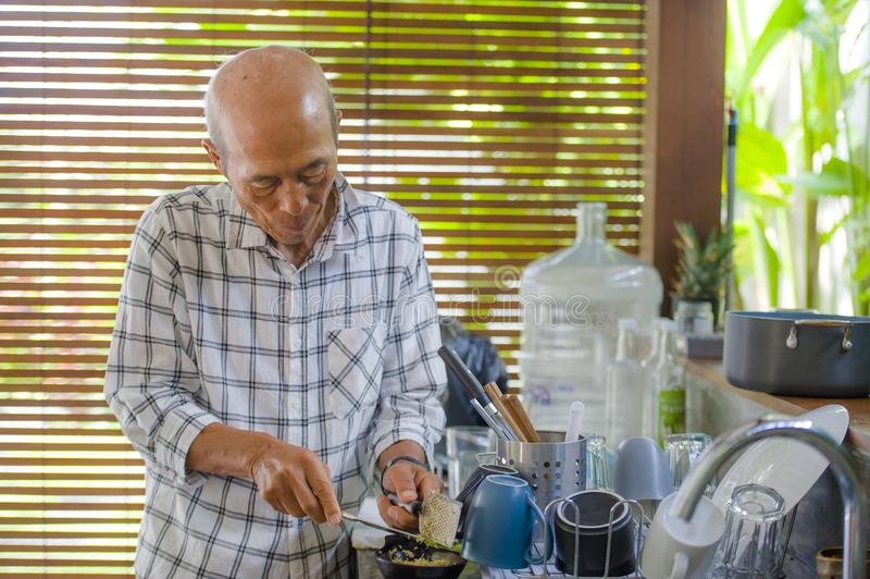 lifestyle portrait of senior happy and sweet Asian Japanese retired man cooking at home kitchen alone neat and tidy enjoying prep royalty free stock photography