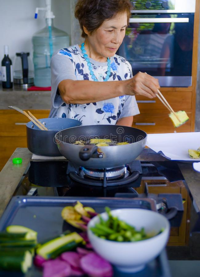 Lifestyle portrait of senior happy and sweet Asian Japanese retired woman cooking at home kitchen alone neat and tidy stock photo