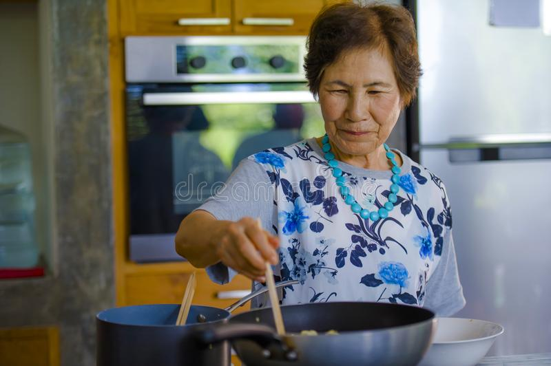 Lifestyle portrait of senior happy and sweet Asian Japanese retired woman cooking at home kitchen alone neat and tidy. Enjoying preparing meal in elderly and stock photo