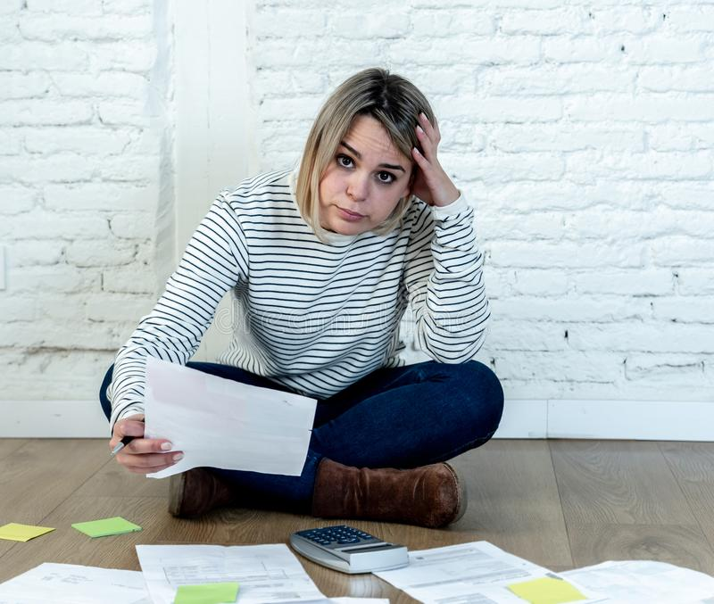 Lifestyle portrait of stressed overwhelmed young woman managing home finances and paying bills. Portrait of worried young woman feeling stressed and desperate on stock photography