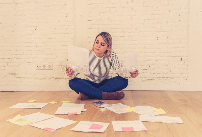 Lifestyle portrait of stressed overwhelmed young woman managing home finances and paying bills. Portrait of worried young woman feeling stressed and desperate on stock photo