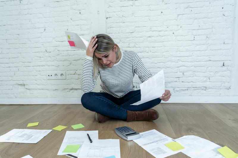 Lifestyle portrait of stressed overwhelmed young woman managing home finances and paying bills. Portrait of worried young woman feeling stressed and desperate on royalty free stock image