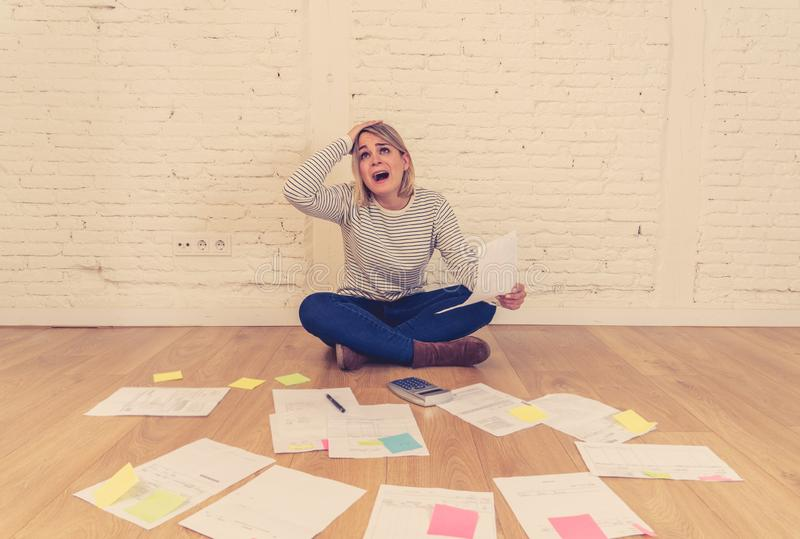 Lifestyle portrait of stressed overwhelmed young woman managing home finances and paying bills. Portrait of worried young woman feeling stressed and desperate on royalty free stock photography