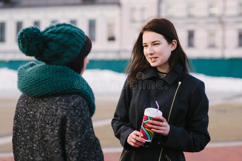 Lifestyle portrait of two female friends standing on the street and talking royalty free stock photo