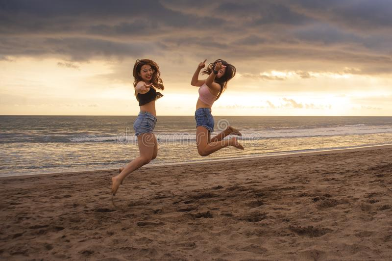 Lifestyle portrait of two happy and attractive young Asian Korean women girlfriends jumping on sunset beach excited and cheerful e stock image