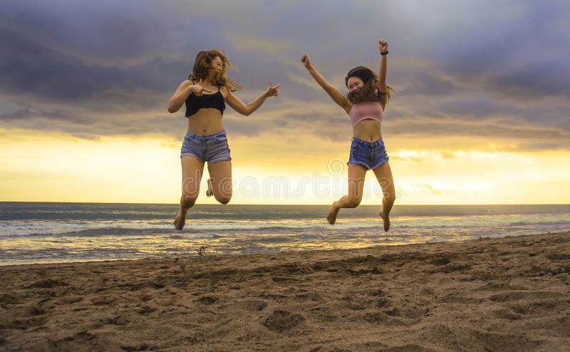Lifestyle portrait of two happy and attractive young Asian Korean women girlfriends jumping on sunset beach excited and cheerful e stock images