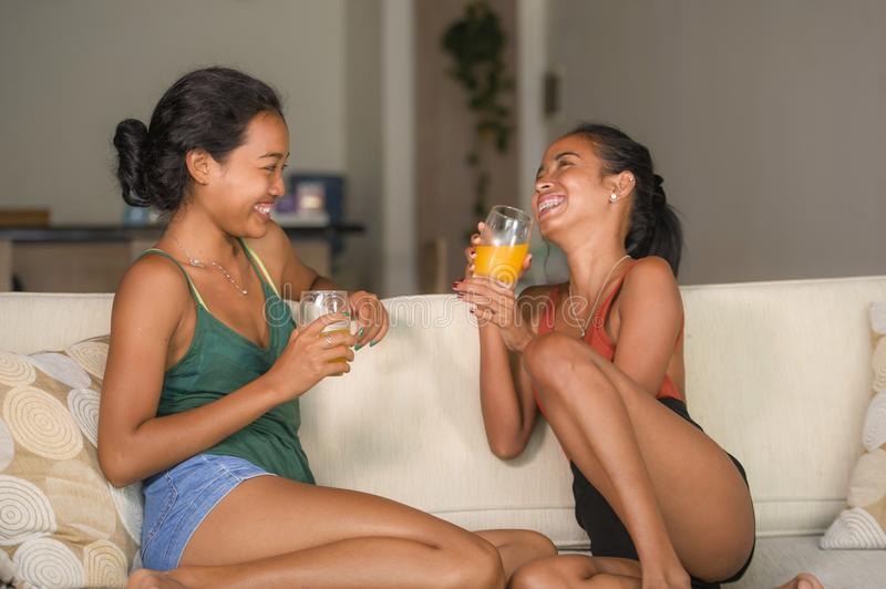 Lifestyle portrait of two young happy and relaxed Asian girlfriends having fun talking laughing and gossiping at home sofa couch s. Haring complicity together in stock image