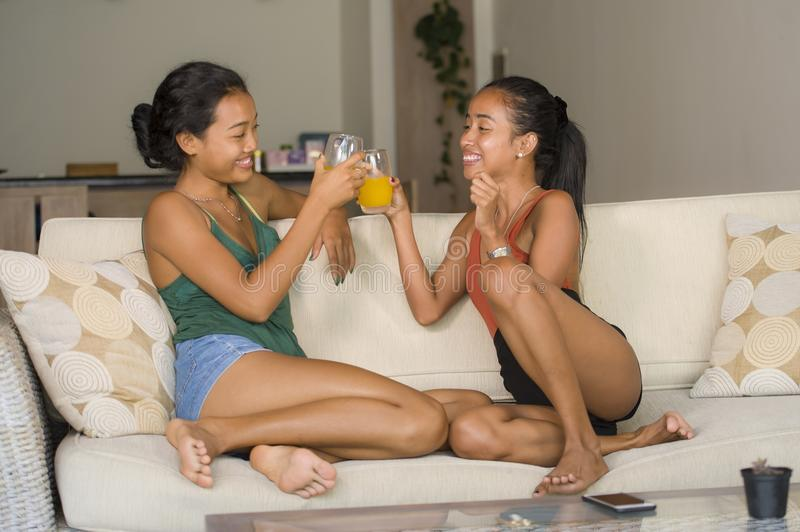 Lifestyle portrait of two young happy and relaxed Asian girlfriends having fun talking laughing and gossiping at home sofa couch s. Haring complicity together in royalty free stock image