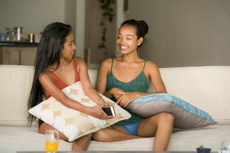 Lifestyle portrait of two young happy and relaxed Asian girlfriends having fun talking laughing and gossiping at home sofa couch s stock photos