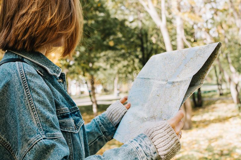 Lifestyle portrait of young adult female in a forest or park holding map in her hands stock photography