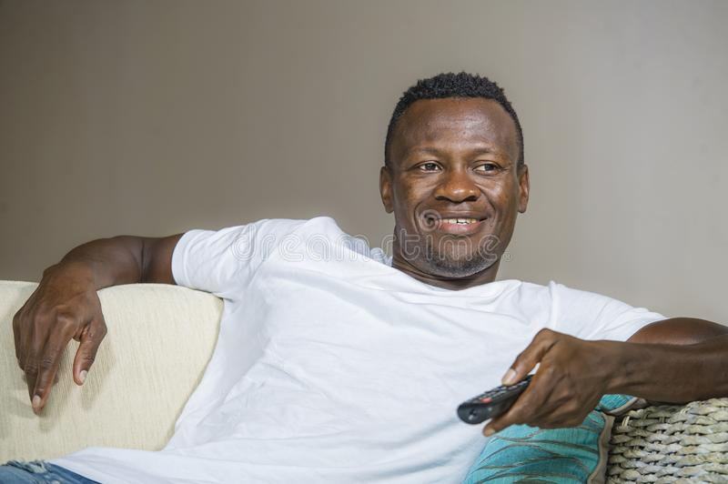 Lifestyle portrait of young attractive and happy black african American man holding TV remote controller watching television movie. Lifestyle candid portrait of stock image