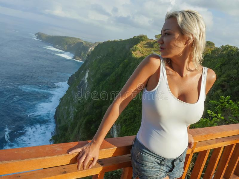 Attractive and happy blond tourist woman looking the stunning view of beautiful sea cliff beach at viewpoint enjoying exotic. Lifestyle portrait of young royalty free stock photography