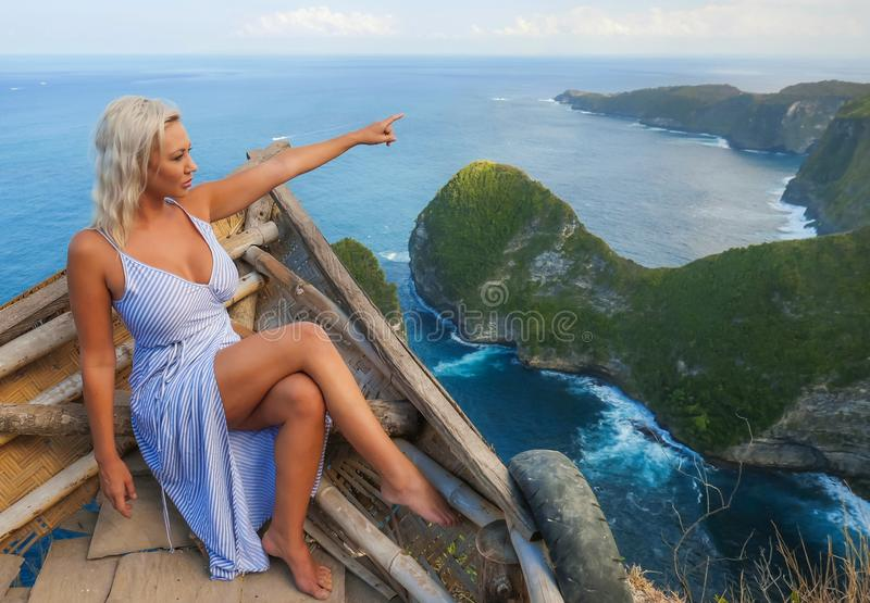 Young attractive and happy tourist woman looking the stunning view of beautiful sea cliff beach at viewpoint enjoying exotic. Lifestyle portrait of young royalty free stock photography